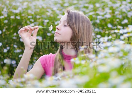 beautiful young girl smelling camomiles - stock photo