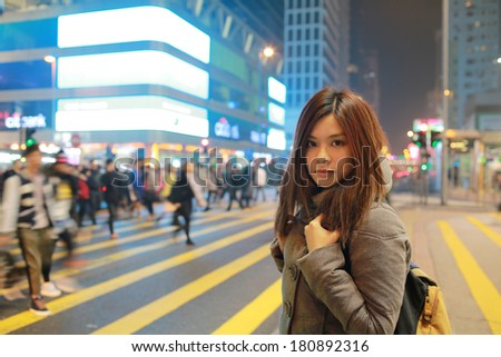 Beautiful young girl stand out and watching at night in hong kong, lost in city , busy crowd and yellow zebra crossing blurred background  - stock photo
