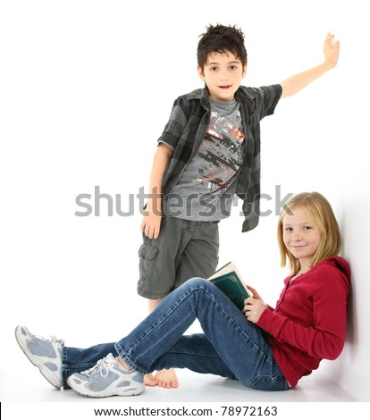Beautiful young girl student with book sitting against the wall.  Boy standing behind her. - stock photo
