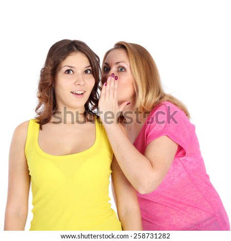 beautiful young girl telling news to her friend - stock photo