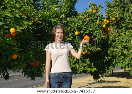 Beautiful young girl under an orange tree
