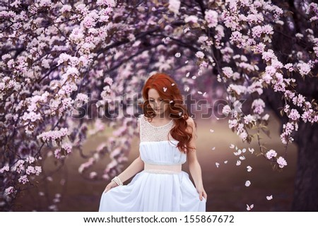 Beautiful young girl under the flowering pink apple-tree - stock photo