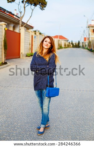Beautiful young girl walking down the street paved with stone near the houses in a small town, street portrait