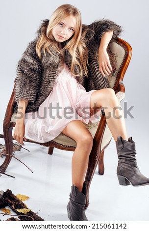 Beautiful young girl wearing fashionable clothes posing in studio. Autumn photo.