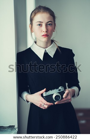 beautiful young girl with a camera - stock photo