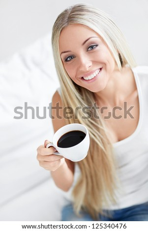 Beautiful young girl with a cup of coffee at home