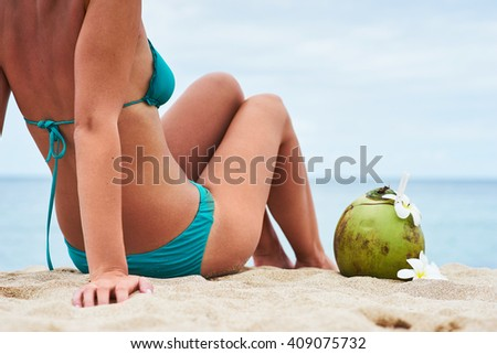 beautiful young girl with a sports figure and tanned body enjoying the sun on a tropical beach with ocean views and fresh coconut with flowers frangipani - stock photo