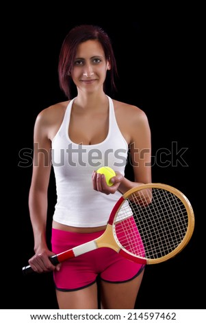 Beautiful young girl with a tennis racquet on a black background.