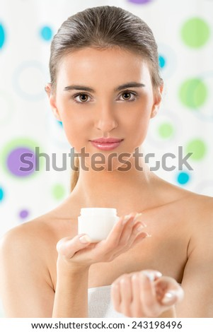 Beautiful young girl with a towel wrapped around her chest, holding cream in her hand and with a slight smile looking at the camera. - stock photo