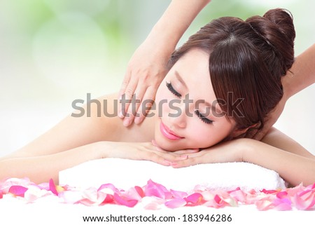 Beautiful young girl with attractive face having a massage for shoulder on resort green background, asian woman