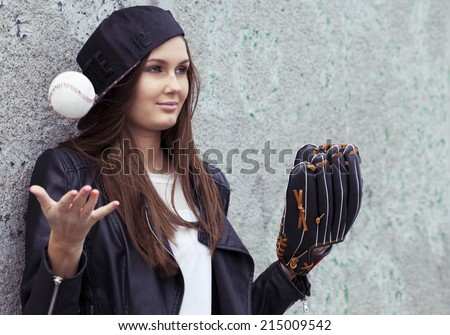 Beautiful young girl with baseball equipment. Urban scene - stock photo