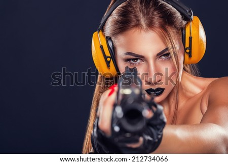 Beautiful young girl with black make-up training with a pistol on a dark background - stock photo