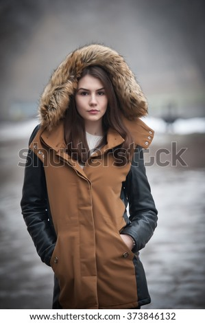 Beautiful young girl with brown coat trimmed with gray fur enjoying the winter scenery in park. Teenage girl with black leather sleeves coat posing in winter concept. Young female bright cold day - stock photo