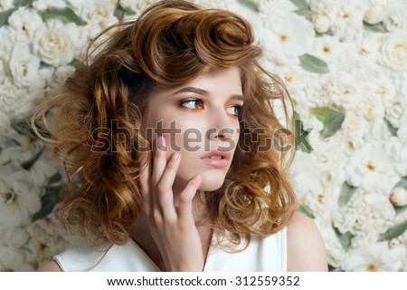 Beautiful young girl with curly hair against white flowers, the concept of beauty  - stock photo