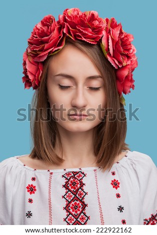 Beautiful young girl with eyes closed in the Ukrainian national suit  - stock photo