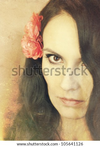 Beautiful young girl with flower in her dark hair - stock photo