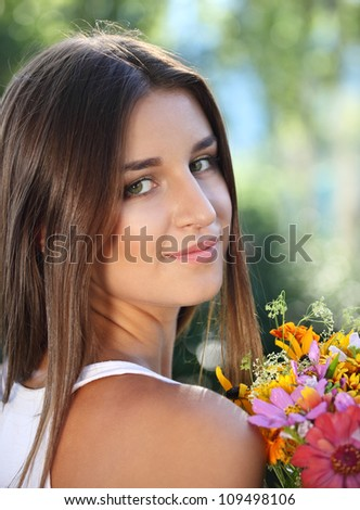 Beautiful young girl with flowers in summer park