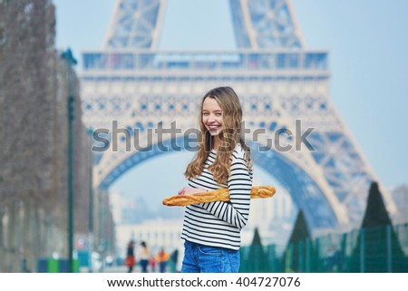 Beautiful young girl with fresh tasty traditional French bread (baguette) near the Eiffel tower - stock photo