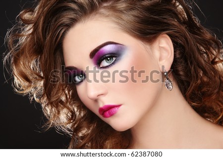 Beautiful young girl with glowing colorful disco make-up and curly hairstyle - stock photo