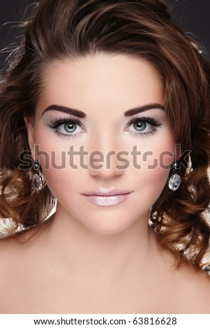 Beautiful young girl with glowing white make-up and curly hairstyle