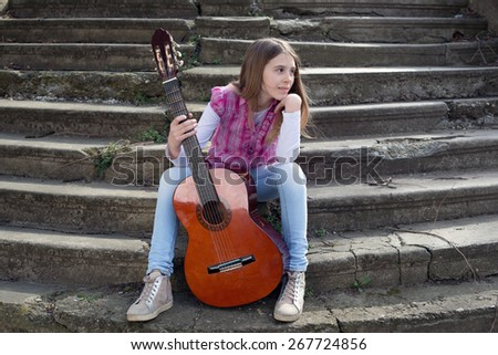 Beautiful Young Girl With Guitar in Front of Her Sitting on the Foot of the Stairs and Looking Thoughtfully at the Horizon - stock photo