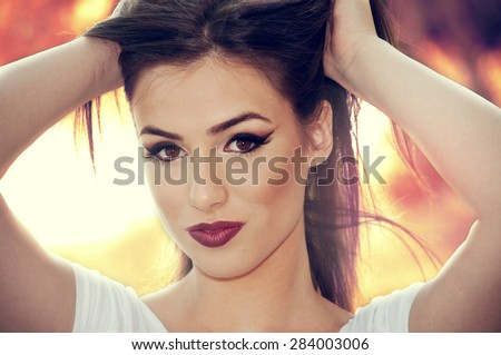 Beautiful young girl with hands in her hair with softly summer colors background - stock photo
