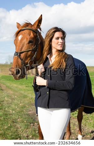 Beautiful young girl with her horse dressing uniform competition: outdoors portrait on sunny day