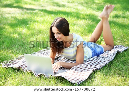 Beautiful young girl with laptop in park - stock photo