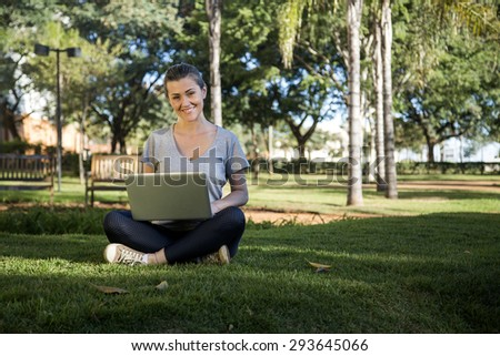 Beautiful young girl with laptop or tablet in park - stock photo