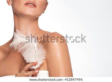 Beautiful young girl with large white feather. clean soft body products. Beauty Portrait. Woman Touching. Perfect Fresh Skin. Youth and Skin Care Concept. Studio shot. Isolated on white background - stock photo