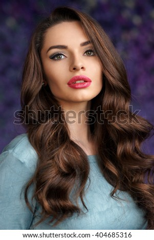 Beautiful young girl with long wavy brunette hair and bright evening make-up looking at you and posing against purple flowers background. Shallow DOF - stock photo