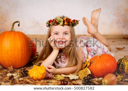 Beautiful young girl with pumpkins