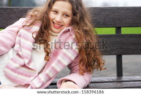 Beautiful young girl with red curly hair relaxing and laying down on a wooden bench in a park during a cold winter day, wearing a pink coat and a scarf, smiling outdoors. - stock photo