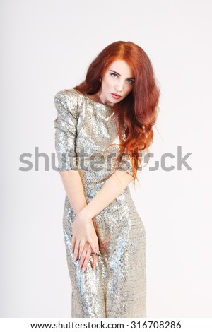 Beautiful young girl with red hair and shiny silver dress standing with hands on hips