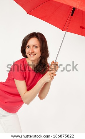 Beautiful young girl with red umbrella posing in studio, white background