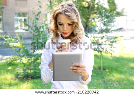 Beautiful young girl with tablet on city street