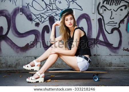 Beautiful young girl, with tattoo on her arm, wearing in cap, sandals, shirt and shorts, posing on her skateboard, near the wall with graffiti, in the park, full body - stock photo