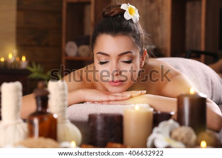 Beautiful young girl with towel lying on massage table and aromatic candles with salt in spa salon - stock photo