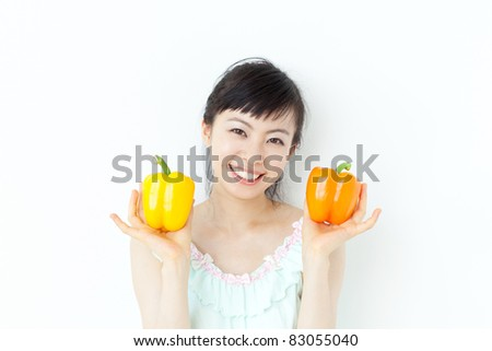 beautiful young girl with two peppers - stock photo