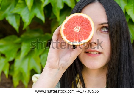 Beautiful young girl without makeup or teenager holding a fruit or of grapefruit in hand