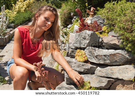Beautiful young girl working in the garden. Young gardener adjusts garden. Summer day in the garden. - stock photo