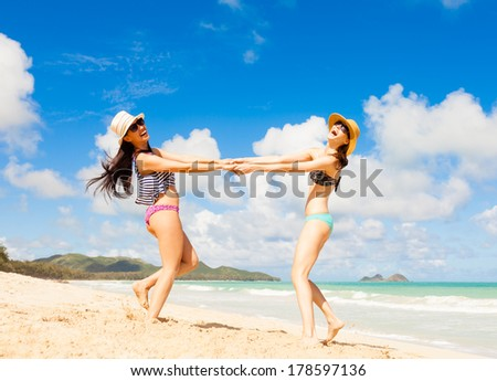 Beautiful young girls dancing on the beach. Beach party. - stock photo