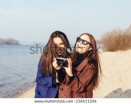 Beautiful young girls taking pictures on the beach in front of the sea. Outdoor lifestyle portrait - stock photo