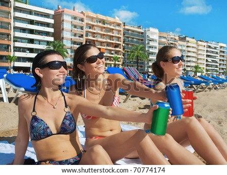 Beautiful young girls with drinks on beach. Costa Brava. Spain - stock photo