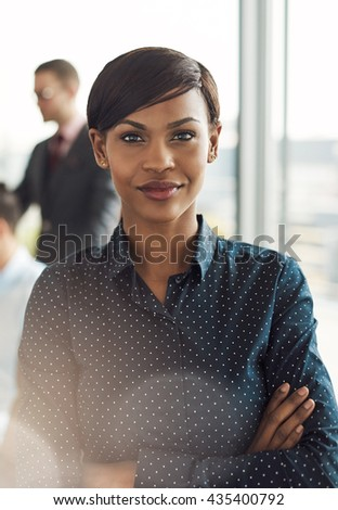 Beautiful young grinning business woman in office with polka dot blouse, folded arms and confident expression as strong light flare shines in front of her - stock photo