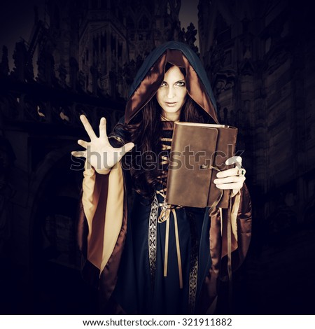 Beautiful young halloween witch wearing vintage gothic dress with hood holding magical book of spells in old leather cover making magic isolated on white background - stock photo