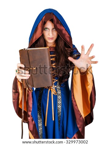 Beautiful young halloween witch wearing vintage gothic dress with hood holding magical book of spells in old leather cover making magic isolated on white background