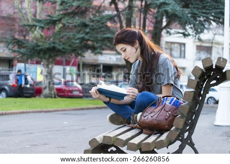 Beautiful young happiness girl sitting on wood bench and reading book in the park. - stock photo