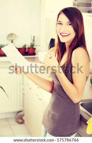 Beautiful young happy caucasian woman in the kitchen drinking something hot and reading bill - stock photo
