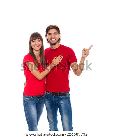 beautiful young happy couple love smiling embracing point finger to empty copy space, man and woman smile looking up wear red t shirt, isolated over white background